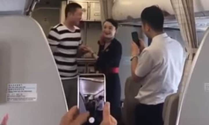 The happy couple deliver the news to cheering passengers. Picture: YouTube Source:YouTube