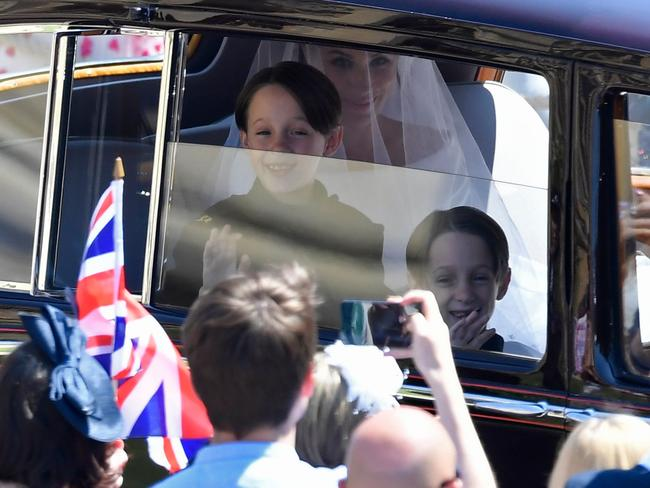 Page boys John and Brian Mulroney wave to the crows as Meghan Markle arrives for the wedding ceremony.
