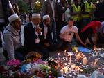 People pray and light candles set up in front of floral tributes in Albert Square in Manchester, northwest England on May 23, 2017. Picture: AFP