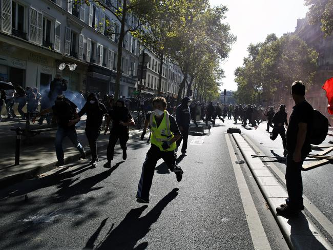 Protesters run away from riot police in Paris. Picture:AP