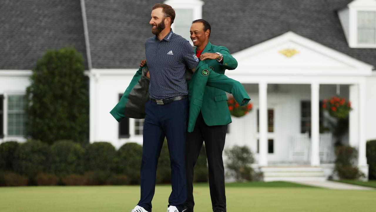 Dustin Johnson is awarded the Green Jacket by Masters champion Tiger Woods. (Photo by Patrick Smith/Getty Images)