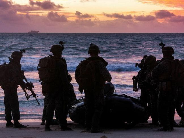 Soldiers from the 2nd Battalion, Royal Australian Regiment and United States Marines during the amphibious assault. HMAS Adelaide is on the horizon. Picture: Defence