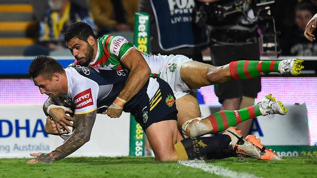 Tariq Sims of the Cowboys scores a try despite being tackled by Greg Inglis.