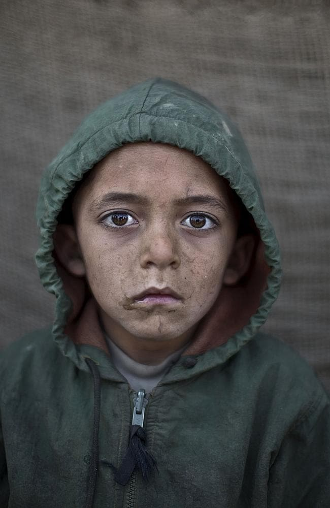IAfghan refugee boy, Waheed Wazir, 6, poses for a picture, while playing with other children in a slum on the outskirts of Islamabad, Pakistan.