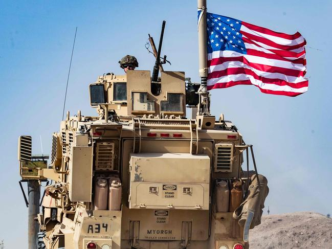 A US soldier sits atop an armoured vehicle during a demonstration by Syrian Kurds against Turkish threats on the outskirts of Ras al-Ain town in Syria's Hasakeh province. Picture: AFP
