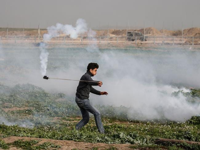 A Palestinian protester uses a slingshot to throw back a tear gas canister at Israeli forces following a demonstration near the fence along the border with Israel, east of Gaza City. Picture: AFP