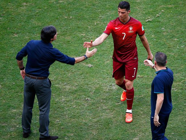 TAKE THAT! Somewhere on that right hand of Germany coach Joachim Loew, left, is a juicy booger awaiting the mitt of unsuspecting megastar Cristiano Ronaldo.