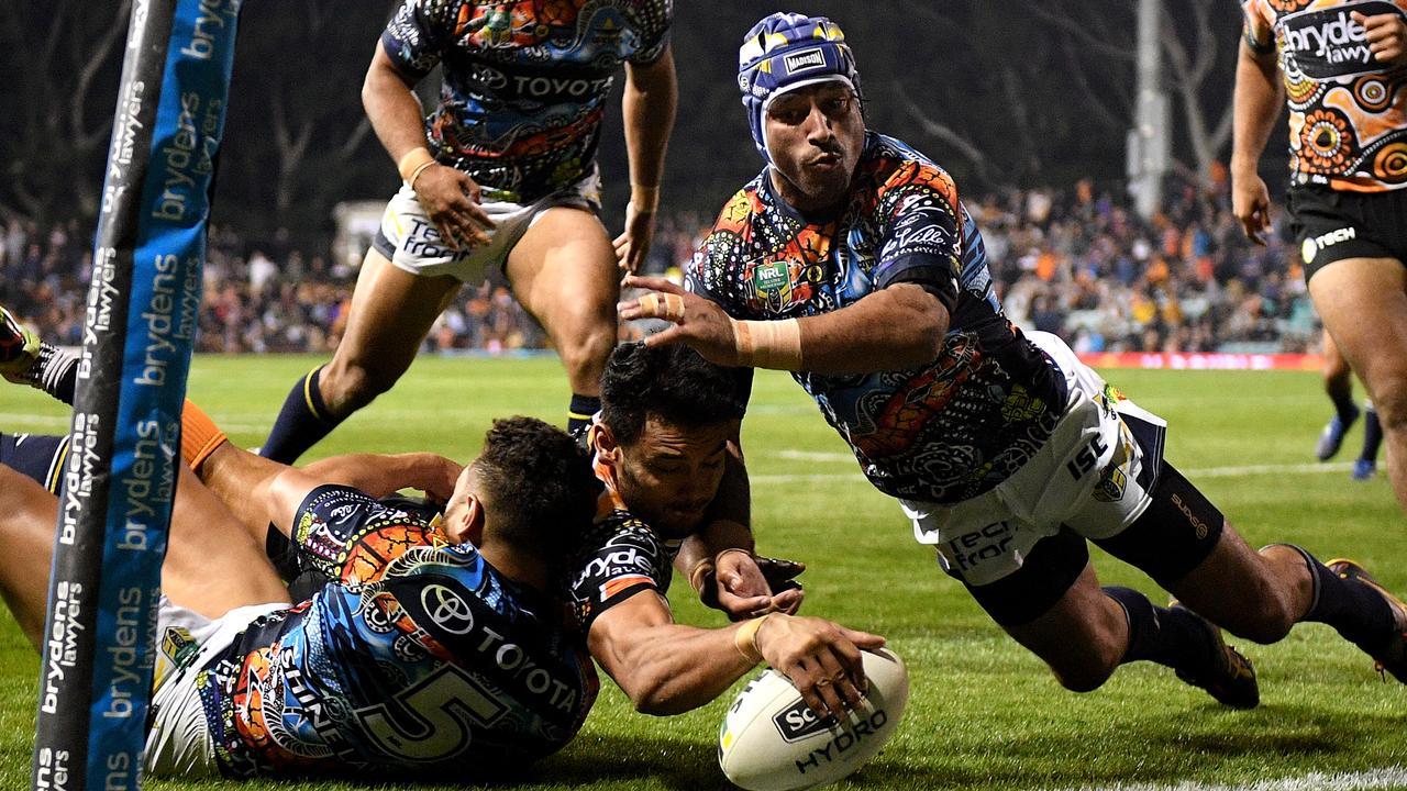 David Nofoaluma of the Tigers scores a try despite an attempted tackle from Johnathan Thurston.