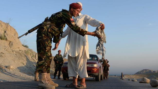 An Afghan National Army (ANA) soldier searches a man at a checkpoint.