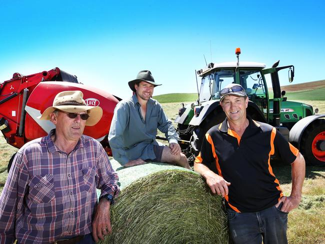 Farmers Phillip Green, from left, Nathan Rabe and Rodney Walker baling silage near Penguin this week. PICTURE CHRIS KIDD