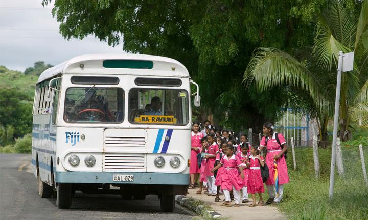 Indian children getting on the school bus in Fiji