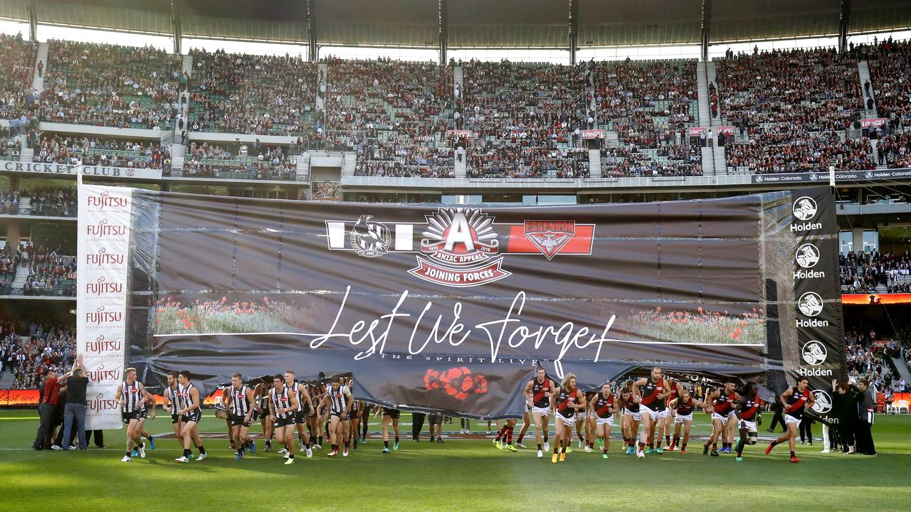 Collingwood and Essendon run through the banner on ANZAC DAY 2018. Photo: Adam Trafford/AFL Media/Getty Images.