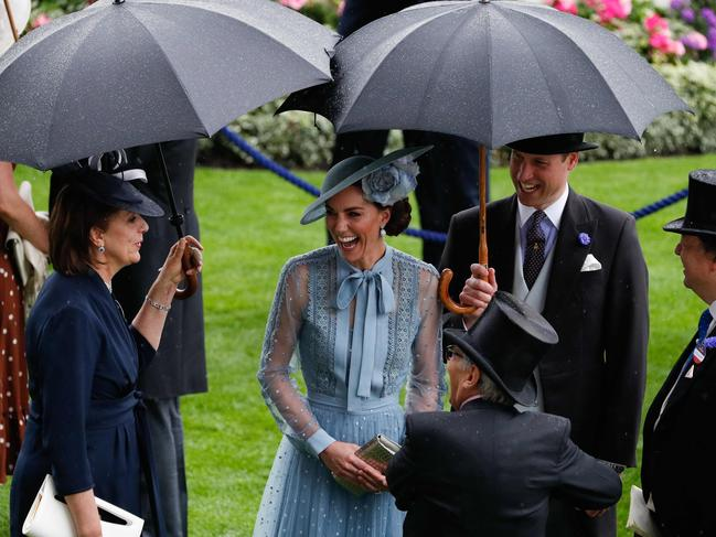 William was happy to shield his wife from the rain as they chatted to guests. Picture: Adrian Dennis/AFP