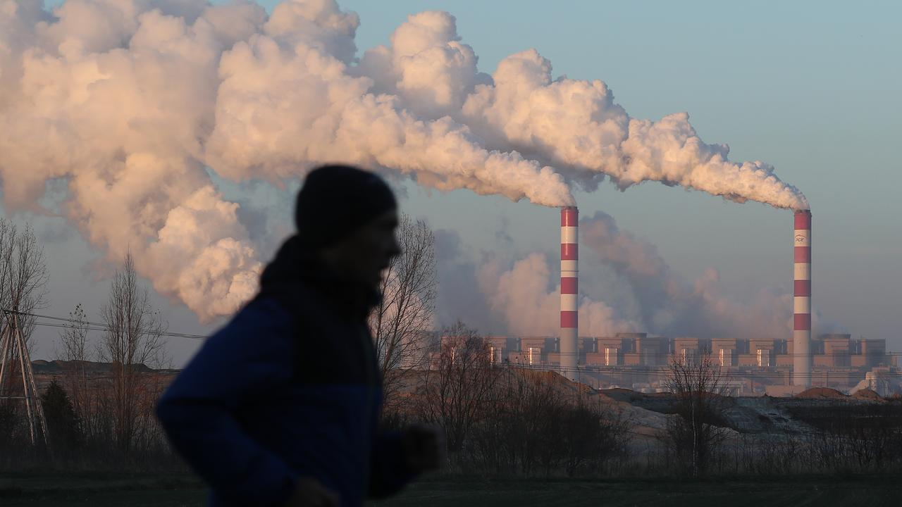 A man jogs through the village of Kleszczow, Poland, as steam and smoke rises from the Belchatow Power Station, which is the world largest lignite coal-fired power station. It is two hours' drive from the UN Climate Conference at Katowice. Picture: Getty Images