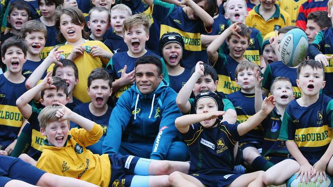 Wallaby halfback Will Genia with young fan at a Wallabies training session in Melbourne on Monday.