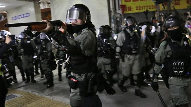 A police officers points his shot un at protesters. Picture: AP