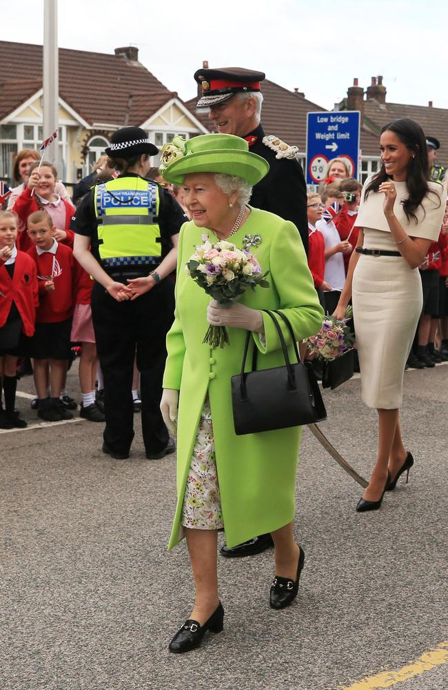 Queen Elizabeth II holds flowers as she shows Meghan, Duchess of Sussex, how she greets the crowds after arriving by Royal Train at Runcorn Station. Picture: Getty