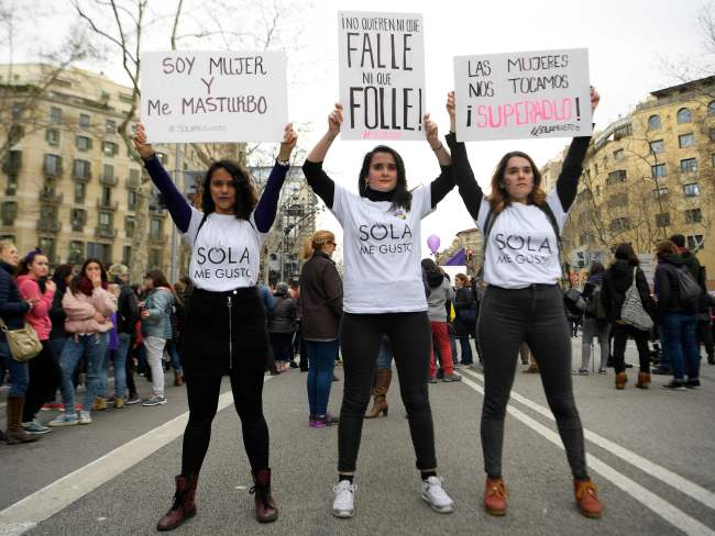 Three women attend a demonstration in Barcelona. Photo: AFP / Lluis Gene