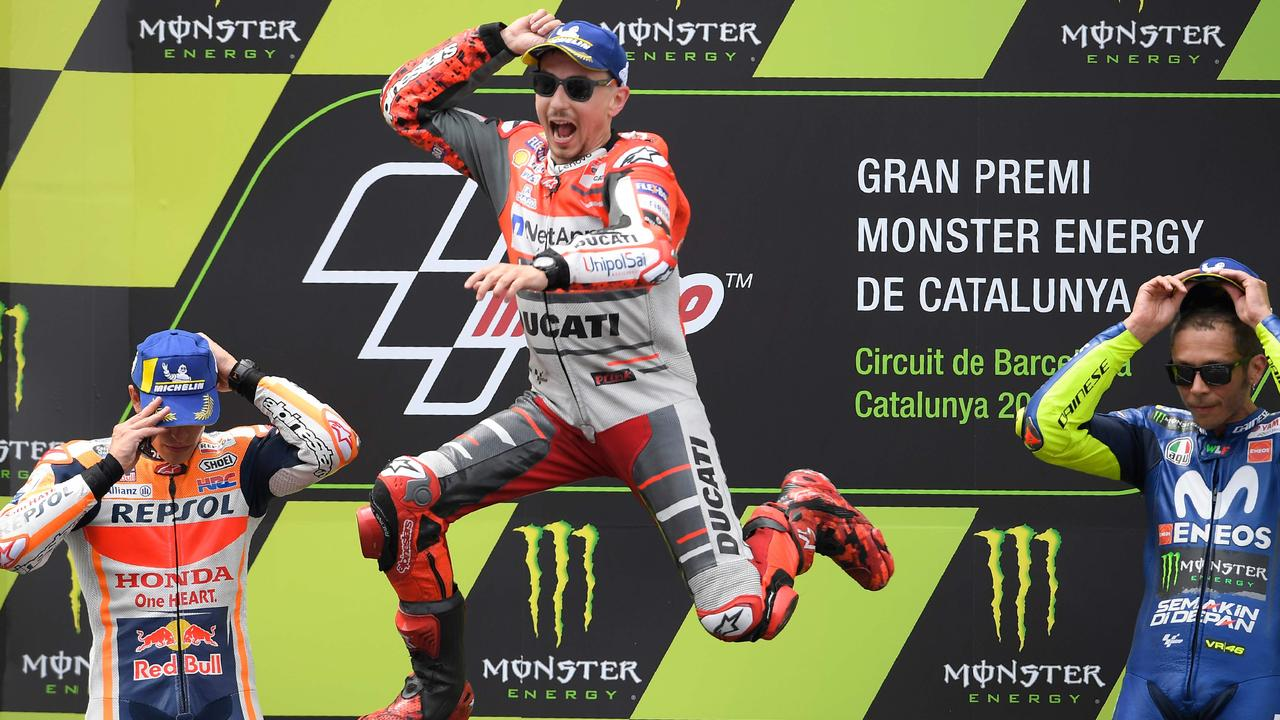 Jorge Lorenzo celebrates on the podium next to Marc Marquez and Valentino Rossi.