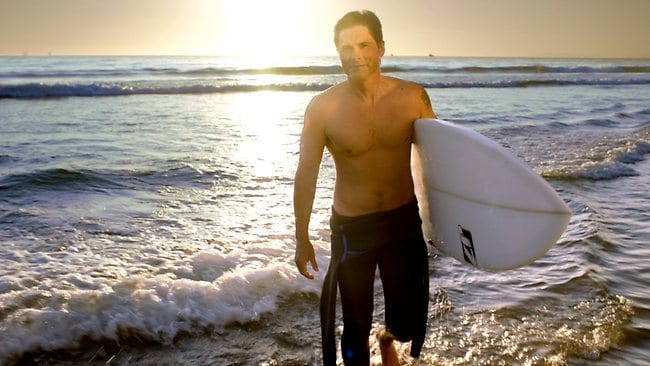 A shirtless Rob Lowe at Morro Bay tries to capture the attention of Australian surfers in the ads promoting California.