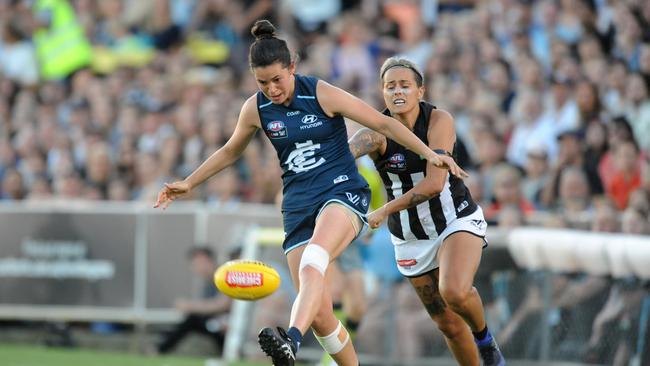 Daniella Hardiman of Carlton kicks the ball ahead of Moana Hope of Collingwood during the round 1 AFLW match between the Carlton Blues and the Collingwood Magpies. Picture: Joe Castro