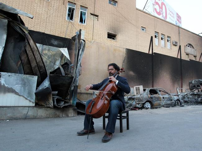 Karim Wasfi, former director for the Iraqi National Symphony Orchestra, plays on his cello next to debris in Baghdad's Sunni Adhamiya district in a symbolic act of protest against violence. AFP PHOTO / SABAH ARAR