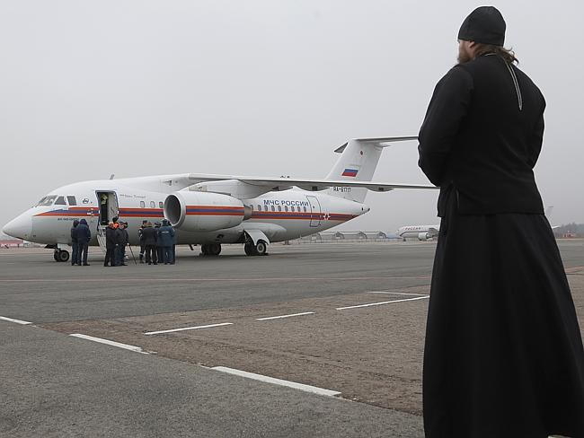 Bless their souls ... An Orthodox priest looks on as a Russian Ministry for Emergency Situations plane carries the bodies of victims from the plane crash.