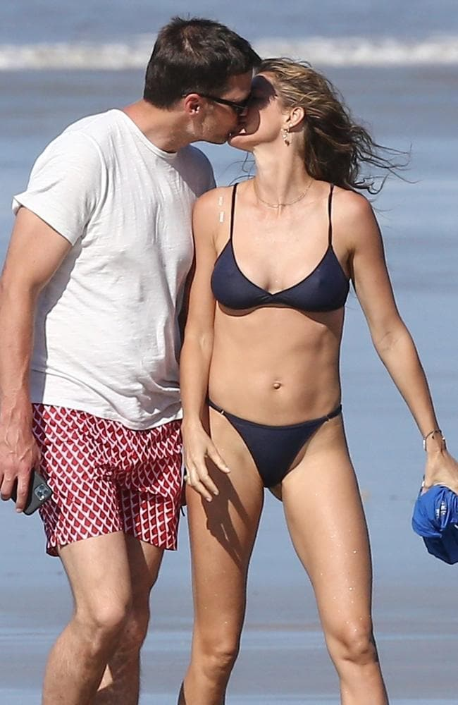 The couple shared a kiss as they walked along the beach. Picture: BACKGRID.