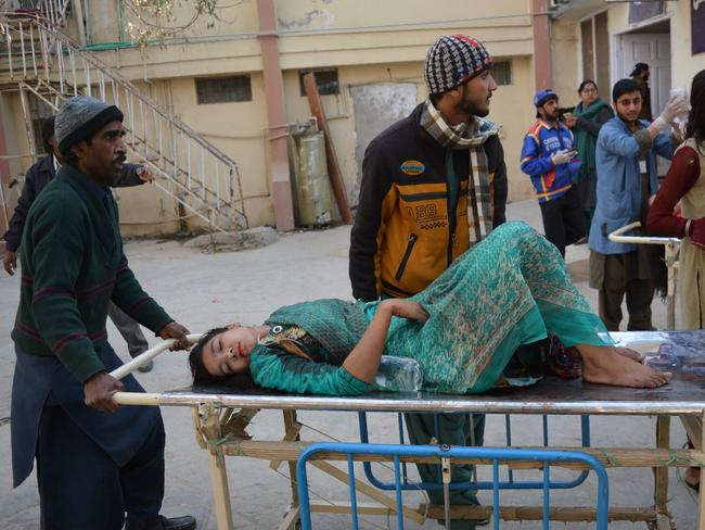 A woman is taken from the scene of a suicide bombing in Pakistan. Picture: AFP/Banaras Khan