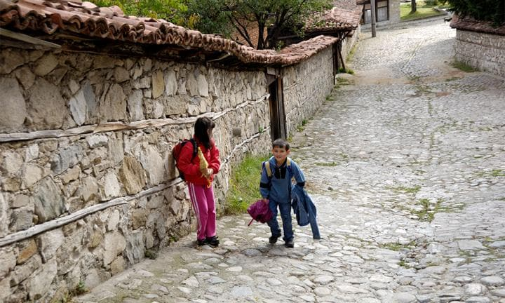 Kids going home after school Koprivshtitsa Bulgaria East Europe