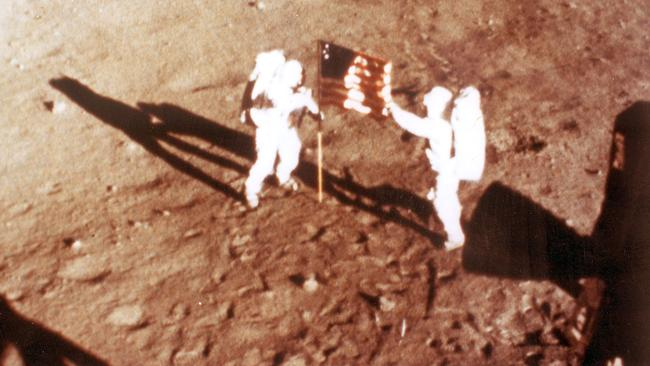 "US astronauts Neil Armstrong and ""Buzz"" Aldrin deploy the US flag on the lunar surface during the Apollo 11 lunar landing mission in 1969."