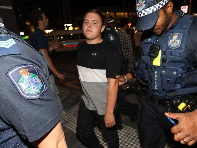 A reveller is escorted by police on the Gold Coast last night. Picture: Mike Batterham