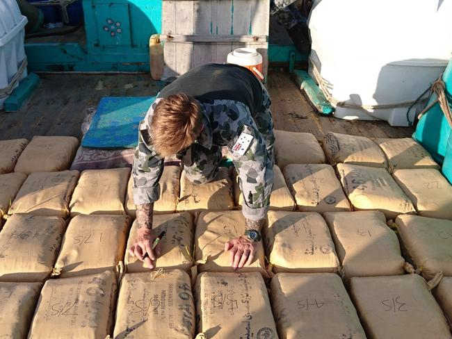 Leading seaman clearance diver Luke Woodcroft from HMAS Warramunga numbers parcels of seized narcotics on the deck of a trafficking vessel. Picture: AAP Image/Supplied/Australian Navy