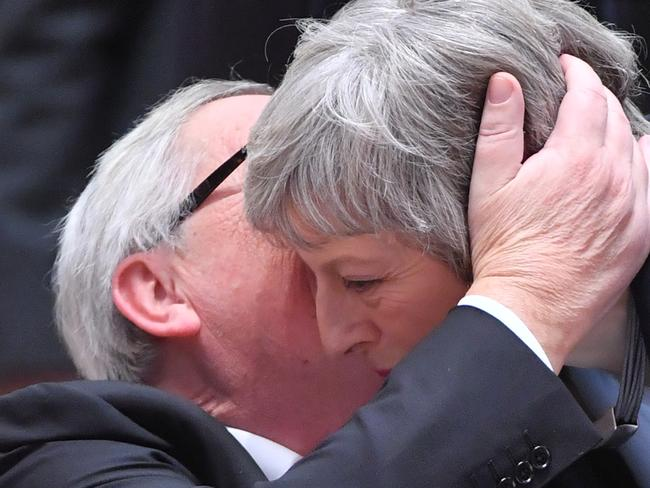 Juncker whispers in the ear of May as she arrived at a European Summit aimed at discussing the Brexit deal. Picture: AFP