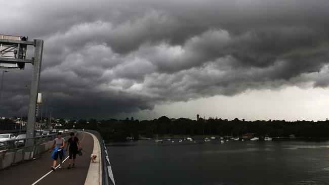 People walk across Iron Cove bridge, Drummoyne, in Sydney's inner west, as storm clouds gather overhead at Iron Cove Bay. Storm cells passed over the city causing widespread flooding and damage.