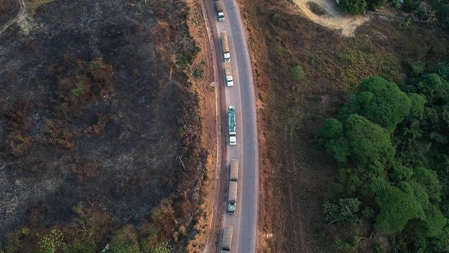Trucks queue along the BR163 highway, in Moraes Almeida district, Itaituba, Para state, Brazil, in the Amazon rainforest. Increased traffic to the region brings other problems. (Photo by Nelson Almeida / AFP)