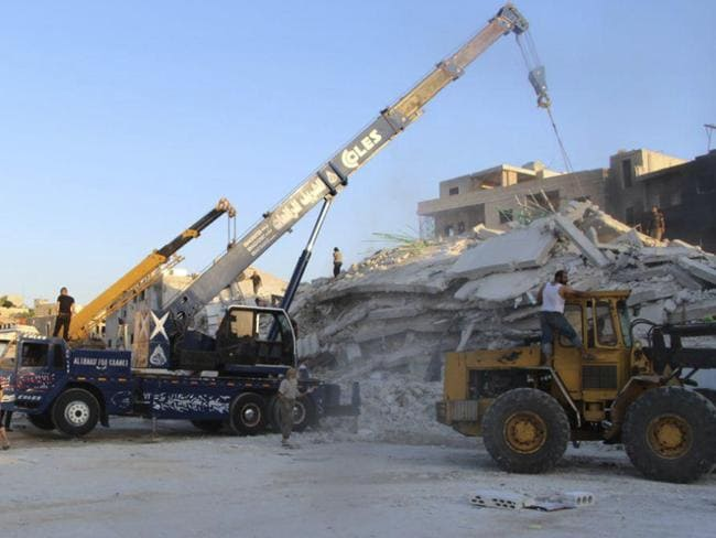 Syrian White Helmet civil defence workers with bulldozers work at the scene of an explosion that brought down a five-story building. Picture; Syrian Civil Defense White Helmets/AP