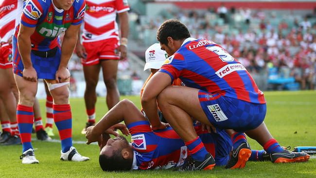 Tautau Moga is treated on the field after the Knights centre suffered a fourth ACL injury in Sunday's loss to the Dragons. Photo: Mark Nolan
