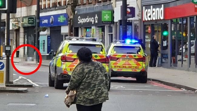The shot man pictured lying outside a Boots while officers stand in the Iceland entrance. Picture: Andy Bullemor/SWNS