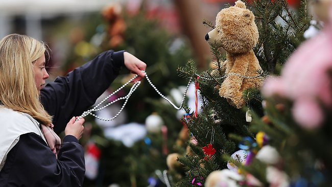 Kat Donohue of Newtown helps to decorate donated Christmas trees placed in front of the Sandy Hook School. Picture: AFP