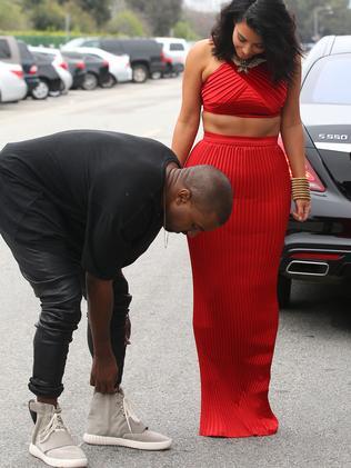 Kanye stops to adjust his custom Yeezy shoes.
