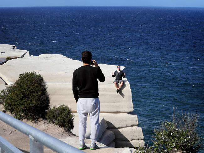 Walkers take pictures near the cliffs edge at Wedding Cake Rock. Picture: John Feder/The Australian.