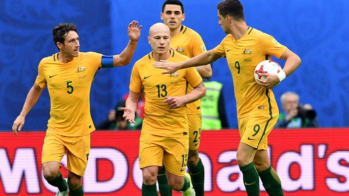 Australia's midfielder Mark Milligan (L) is congratulated by midfielder Aaron Mooy (C) and forward Tomi Juric afetr scoring in a penalty during the 2017 Confederations Cup group B football match between Cameroon and Australia at the Saint Petersburg Stadium on June 22, 2017. / AFP PHOTO / Mladen ANTONOV