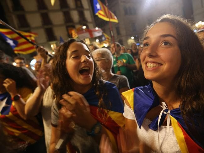 People wave Catalan independence flags while they gather in front of the Palau de la Generalitat de Catalunya, the building that houses the Catalonian presidency. Picture: Getty