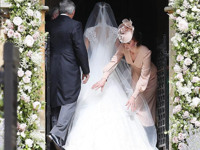 Catherine, Duchess of Cambridge, right, arranges the train of her sister of her sister Pippa Middleton as she arrives with her father Michael Middleton for her wedding to James Matthews. Picture: Getty