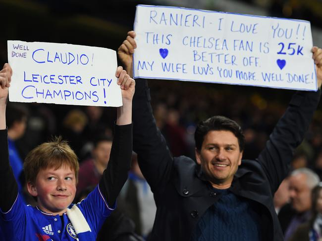 Chelsea fans hold up banners celebrating Leicester City being crowned champions.
