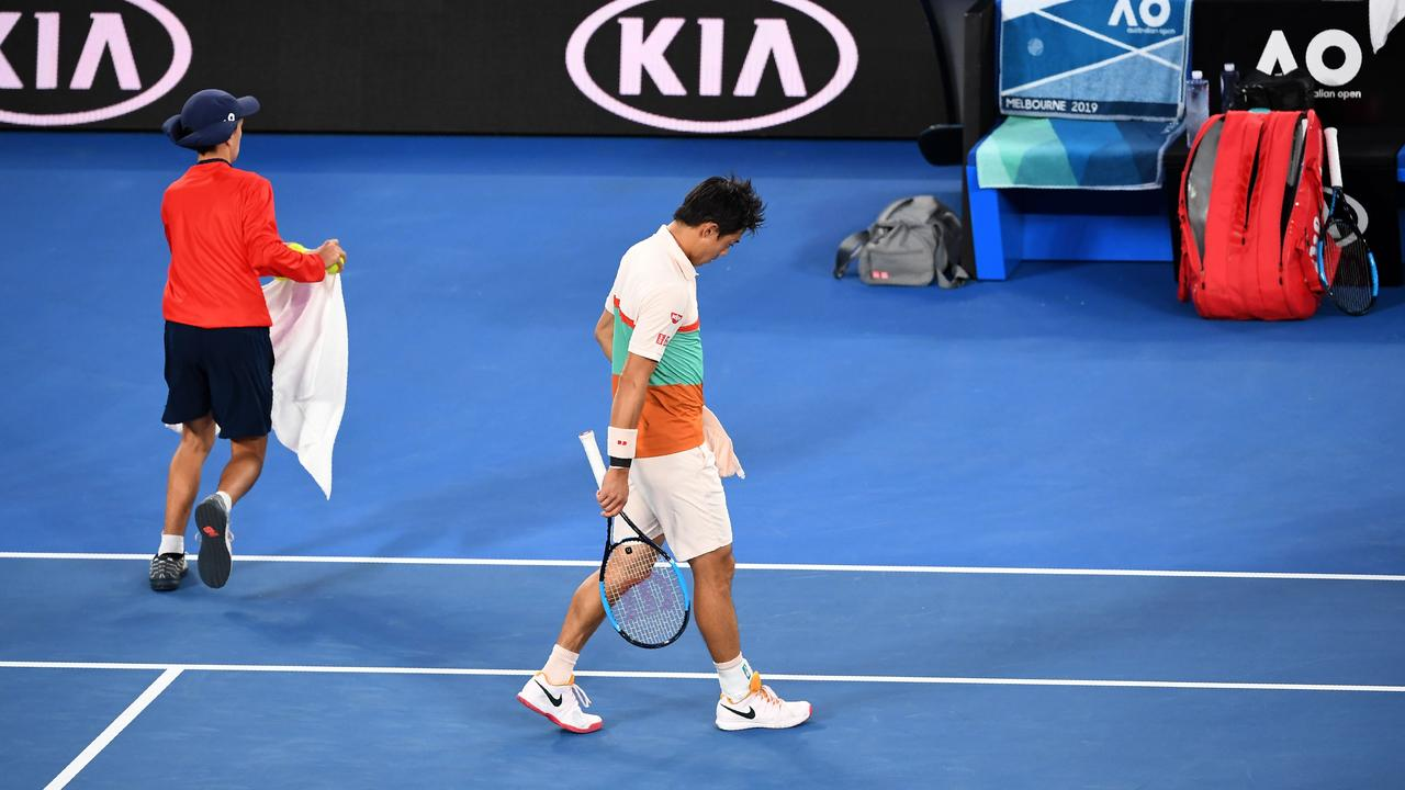 A dejected Kei Nishikori walks off court as he retires from his men's singles quarter-final match against Novak Djokovic.