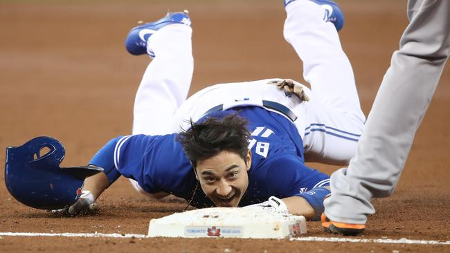 Darwin Barney #18 of the Toronto Blue Jays crawls into third base after stumbling.