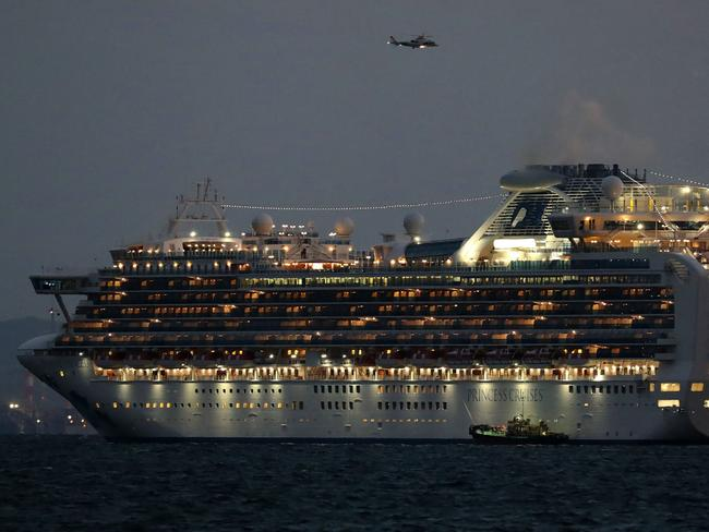 A small boat is pictured next to the Diamond Princess as it sits anchored in quarantine off the port of Yokohama. Picture: STR/JIJI PRESS/AFP
