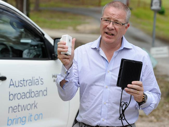 NBN principal technology officer, Tony Cross, with a DPU and a plug-in power pack used in the home of the customer.